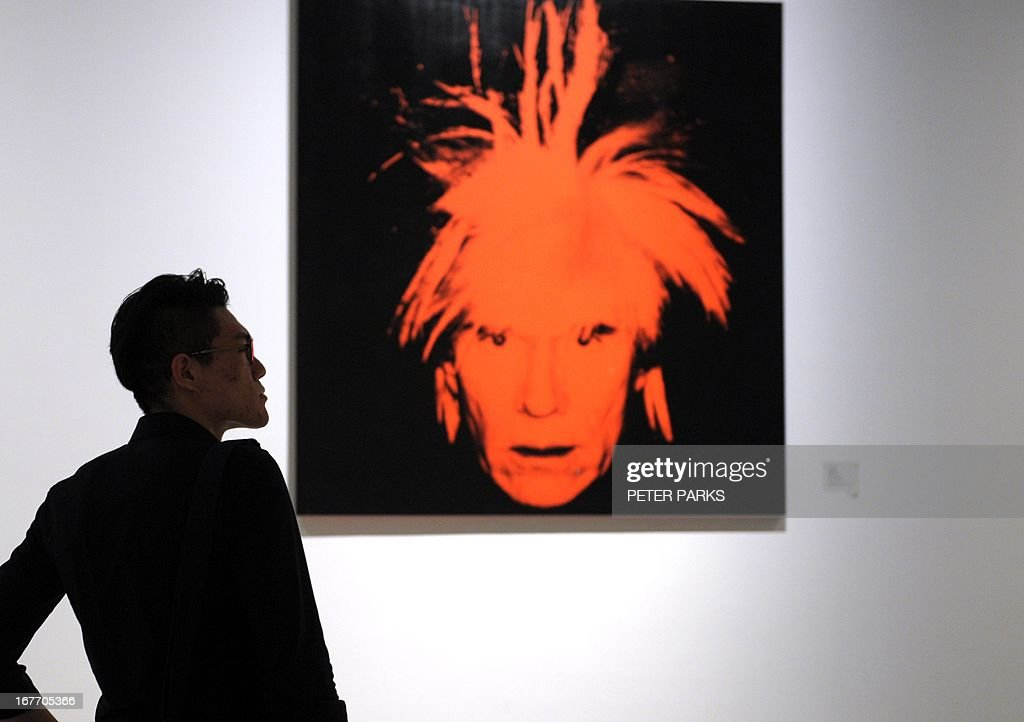 A visitor looks at works of art by US pop artist Andy Warhol at the exhibition 'Andy Warhol: 15 Minutes Eternal' showing at Shanghai's government-funded 'Power Station of Art' in Shanghai on April 28, 2013. Shanghai's contemporary art museum opened the show featuring the works of Warhol, but without his iconic portraits of former Chinese leader Chairman Mao. AFP PHOTO / Peter PARKS