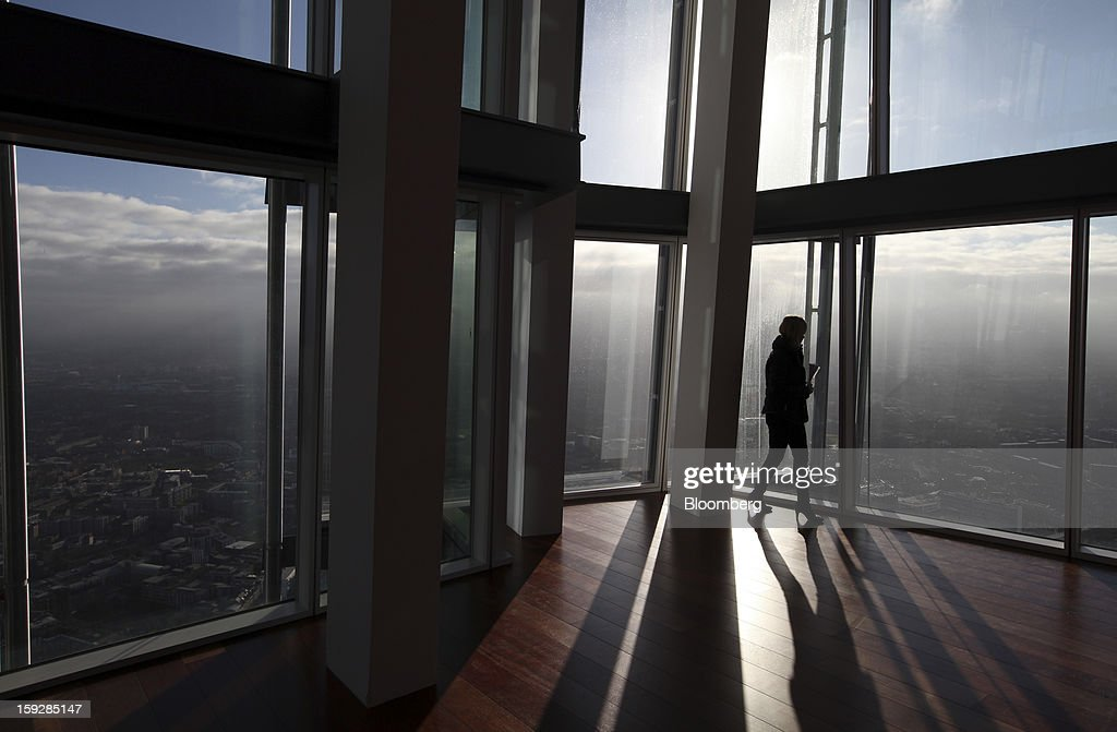 A visitor looks from a window at 'The View From The Shard', a series of viewing galleries near the top of the Shard tower in London, U.K., on Wednesday, Jan. 9, 2013. The Shard, which stands at 309.6 meters on London's South Bank, is owned by LBQ Ltd., which brings together the State of Qatar (the majority shareholder) and Sellar Property Group Ltd., with non-equity funding by Qatar National Bank. Photographer: Chris Ratcliffe/Bloomberg via Getty Images