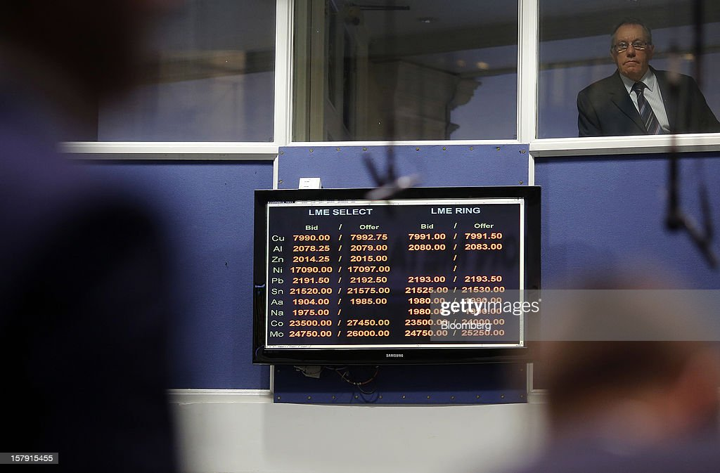 A visitor looks from a window next to a electronic display board suspended above the trading floor of the London Metal Exchange (LME) in London, U.K., on Friday, Dec. 7, 2012. The London Metal Exchange's $2.2 billion takeover by the Hong Kong Exchanges & Clearing Ltd. was completed yesterday. Photographer: Simon Dawson/Bloomberg via Getty Images
