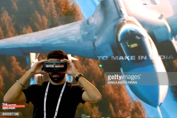 A visitor looks into a pair of virtual reality glasses on the SAAB stand in the exhibition area on the third day of the 11th edition of 'Aero India'...