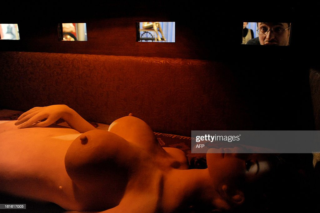 A visitor (R) looks into a window as he tours the 'MuzEros', a museum of erotica, shortly after its opening in the Russia's second city of St. Petersburg, on February 13, 2013. The museum exhibits a collection of sexual artifacts from around the world, the museum organizers said.