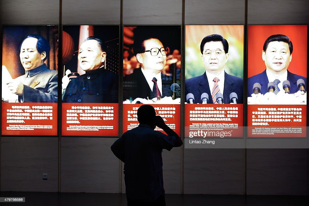 A visitor looks on front portraits of former Chinese leaders Mao Zedong Deng Xiaoping Jiang Zemin Hu Jintao and current President Xi Jinping are seen...