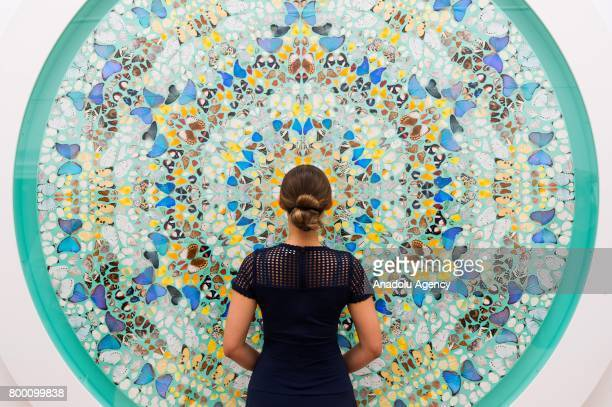 A visitor looks on the artwork titled Contemplation by artist Damien Hirst with a sale estimate of £700000£900000 in London United Kingdom on June 23...