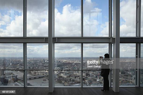 A visitor looks out at the Thames River and the city center in this aerial view taken from The Shard on March 21 2014 in London United Kingdom The...