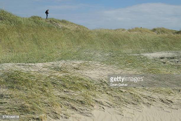 A visitor looks out from the top of a dune near the beach on July 18 2016 at SanktPeterOrding Germany SanktPeterOrding is among the top destinations...