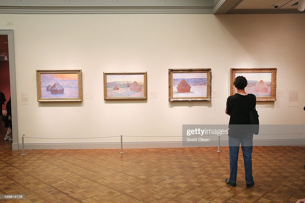 A visitor looks over Claude Monet's series of paintings Stack of Wheat at the Art Institute of Chicago on September 17 2014 in Chicago Illinois The...