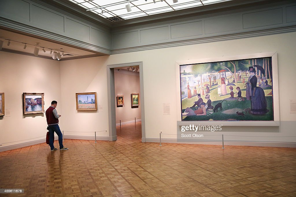 A visitor looks over paintings including Georges Seurat's A Sunday on La Grande Jatte at the Art Institute of Chicago on September 17 2014 in Chicago...