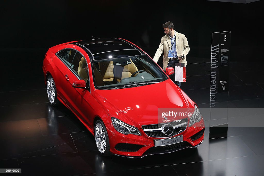 A visitor looks over the new Mercedes E-Class Coupe during the media preview at the North American International Auto Show on January 15, 2013 in Detroit, Michigan. The auto show will be open to the public January 19-27.