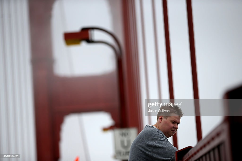 A visitor looks over the railing on the Golden Gate Bridge on June 27, 2014 in San Francisco, California. The Golden Gate Bridge district's board of directors voted unanimously to approve a $76 million funding package to build a net suicide barrier on the iconic span. Over 1,500 people committed suicide by jumping from the iconic bridge since it opened in 1937. 46 people jumped to their death in 2013.