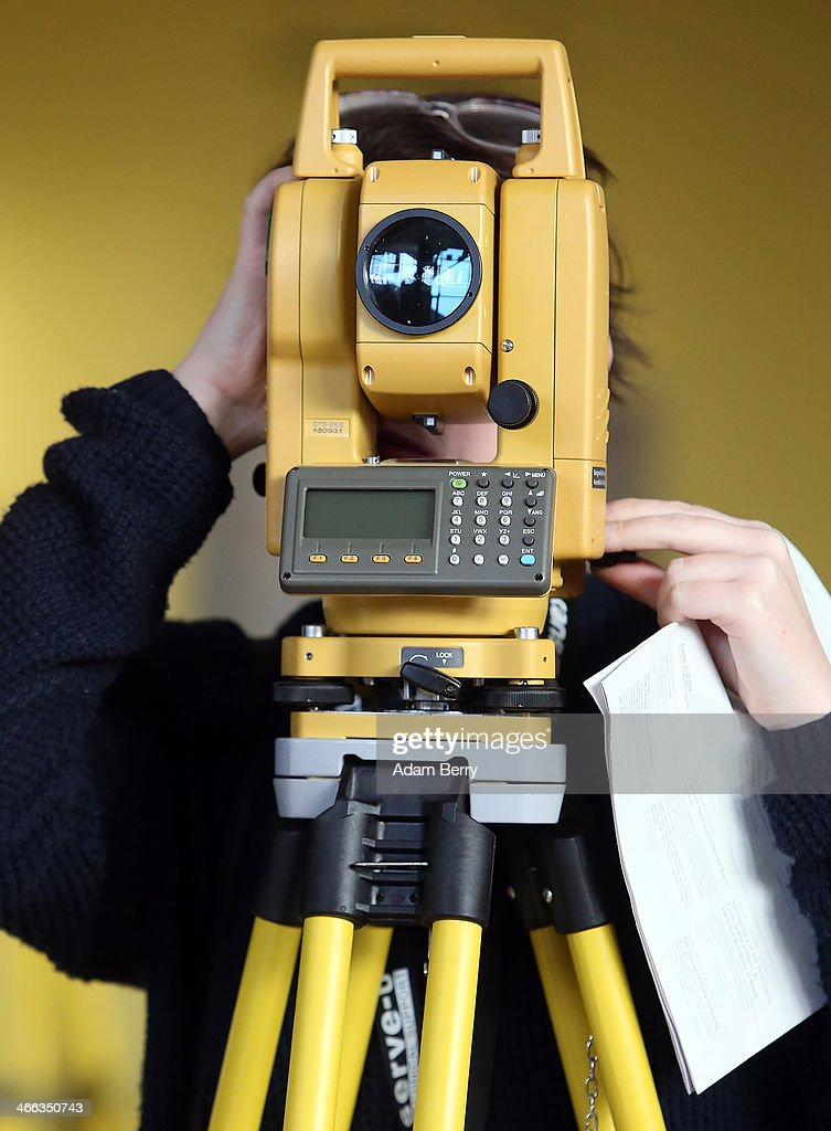 A visitor looks through a theodolite scope, part of the artwork 'Go Forth and Survey' by David Gaulthier and Jaime Allen, at the Transmediale festival for art and digital culture on February 1, 2014 in Berlin, Germany. The festival and year-round project is an attempt to draw out new connections between art, culture and technology.