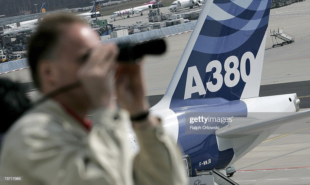 A visitor looks through binoculars from a viewing platform close to a parked Airbus A380 at Frankfurt Airport on March 27, 2007 in Frankfurt, Germany. The 555-seat double-decker A380 returned from a test flight of Lufthansa and Airbus Industries from Washington to test airport function and compatibility of the world's largest passenger aircraft.