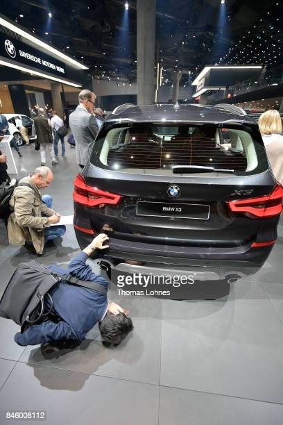 A visitor looks under a BMW X3 car at the 2017 Frankfurt Auto Show on September 12 2017 in Frankfurt am Main Germany The Frankfurt Auto Show is...