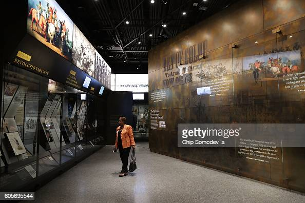 A visitor moves through the Military History Gallery on the third floor Community Galleries at the Smithsonian's National Museum of African American...