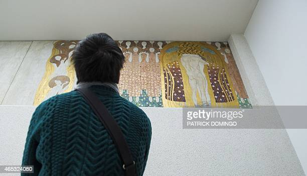 A visitor of the Secession Museum looks at a part of the socalled Beethoven Frieze Painting entitled 'Kiss to the Whole World' by Austrian painter...