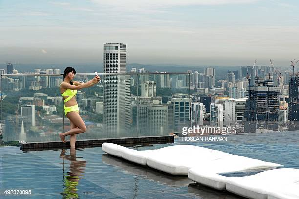 A visitor on the rooftop pool of Marina Bay Sands resort hotel takes a selfie in front of the city skyline in Singapore on May 20 2014 Singapore's...