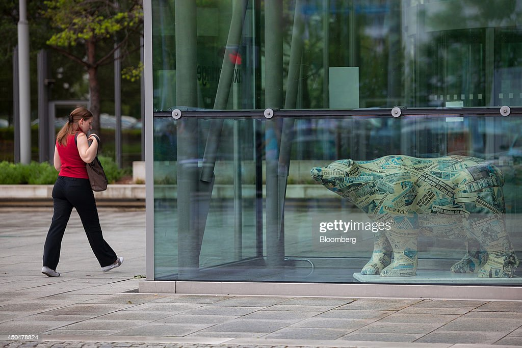 A visitor passes a bear sculpture, covered with newspaper clippings, at the offices of publisher Axel Springer SE in Berlin, Germany, on Wednesday, June 11, 2014. Axel Springer, Europe's biggest newspaper publisher, is working with JPMorgan Chase & Co. and Citigroup Inc. on an initial public offering of its digital-classifieds business, people familiar with the matter said. Photographer: Krisztian Bocsi/Bloomberg via Getty Images