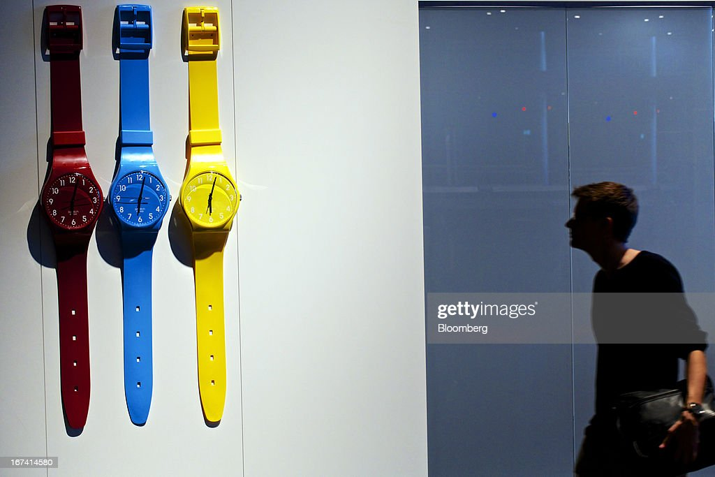 A visitor passes a display of giant wristwatches on a wall outside Swatch Group AG's booth during the Baselworld watch fair in Basel, Switzerland, on Wednesday, April 24, 2013. The annual fair attracts 2,000 companies from the watch, jewelry and gem industries to show their new wares to more than 100,000 visitors. Photographer: Gianluca Colla/Bloomberg via Getty Images