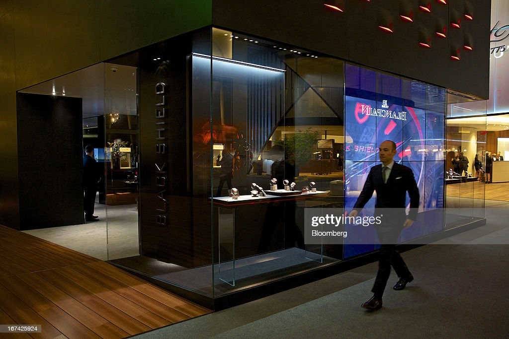 A visitor passes a display of wristwatches at the Tudor booth during the Baselworld watch fair in Basel, Switzerland, on Thursday, April 25, 2013. The annual fair attracts 2,000 companies from the watch, jewelry and gem industries to show their new wares to more than 100,000 visitors. Photographer: Gianluca Colla/Bloomberg via Getty Images