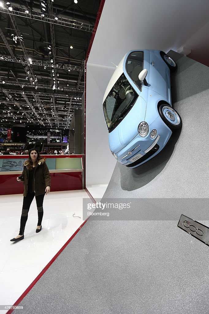A visitor passes a Fiat 500 automobile, produced by Fiat SpA, mounted to the wall of the company's stand on day two of the 84th Geneva International Motor Show in Geneva, Switzerland, on Wednesday, March 5, 2014. The International Geneva Motor Show runs from Mar. 4, and will showcase the latest models from the world's top automakers. Photographer: Chris Ratcliffe/Bloomberg via Getty Images