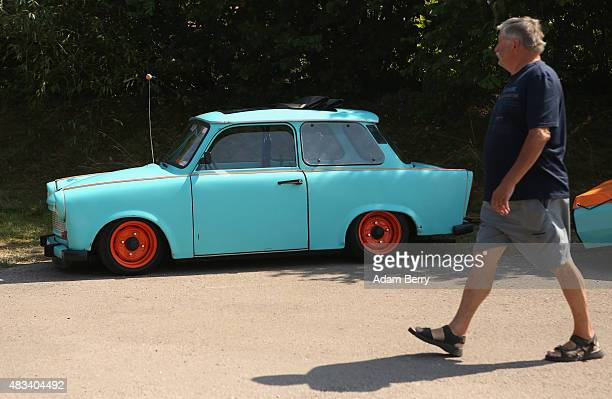 A visitor passes a Trabant automobile at a Trabant enthusiasts' weekend on August 8 2015 near Nossen Germany The Trabant also called the Trabi is the...