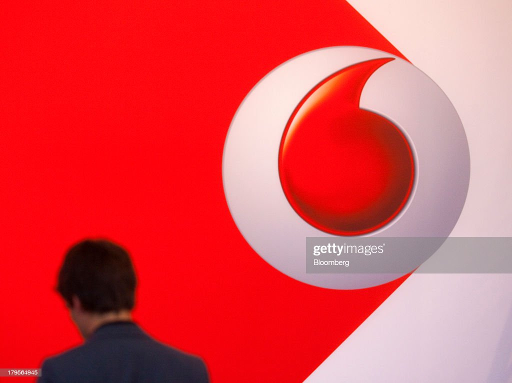 A visitor passes a Vodafone Group Plc logo as it sits on display on the eve of the opening of the IFA consumer electronics show in Berlin, Germany, on Thursday, Sept. 5, 2013. Samsung showed the Galaxy Gear yesterday at IFA, Europe's largest consumer-electronics show, as it races Apple and Sony Corp. to carve a share of the market for wearable technology amid slowing growth in smartphones. Photographer: Krisztian Bocsi/Bloomberg via Getty Images