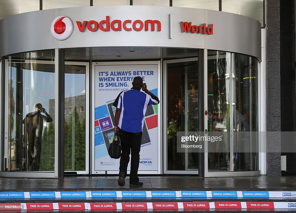A visitor passes advertising for Nokia Lumia 820 smartphones at the entrance to the headquarters of Vodacom Group Ltd., Vodafone's biggest African business, in Johannesburg, South Africa, on Monday, January 28, 2013. Almost two decades after Vodafone Group Plc entered Africa, the region -- where most people earn less than $2 a day and mobile phone towers run on diesel -- is turning into one of the company's biggest profit generators. Photographer: Nadine Hutton/Bloomberg via Getty Images