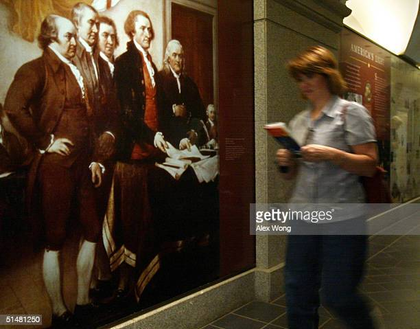 A visitor passes by a picture named 'The Declaration of Independence' by John Trumbull showing members of the committee appointed by the Continental...