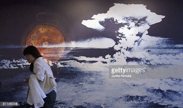 A visitor passes by a wall displaying a picture of the mushroom cloud pictured when the atomic bomb was dropped on August 5 2004 in Hiroshima Japan...
