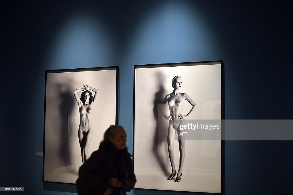 A visitor passes by photos by German-Australian photographer Helmut Newton during a press preview of the 'White women / Sleepless nights / Big nudes' exhibition at the Palazzo delle Esposizioni on March 5, 2013 in Rome. The exhibition will run from March 6 to July 21, 2013.