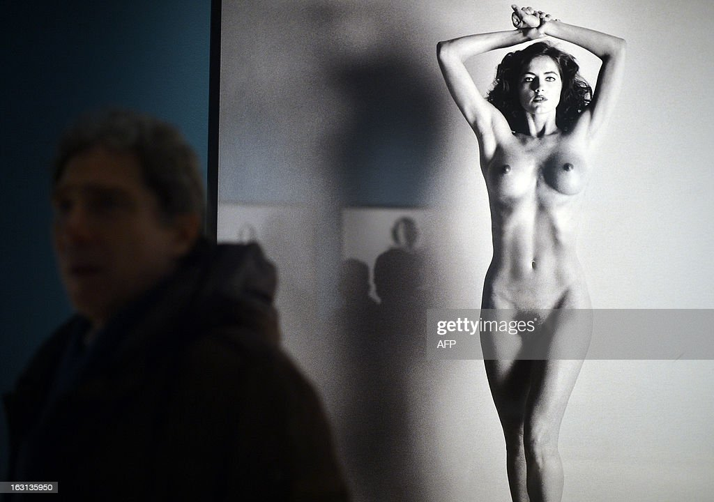 A visitor passes by pictures by German-Australian photographer Helmut Newton during a press preview of the 'White women / Sleepless nights / Big nudes' exhibition at the Palazzo delle Esposizioni on March 5, 2013 in Rome. The exhibition will run from March 6 to July 21, 2013. AFP PHOTO / GABRIEL BOUYS RESTRICTED TO EDITORIAL USE, MANDATORY CREDIT OF THE ARTIST, TO ILLUSTRATE THE EVENT AS SPECIFIED IN THE CAPTION