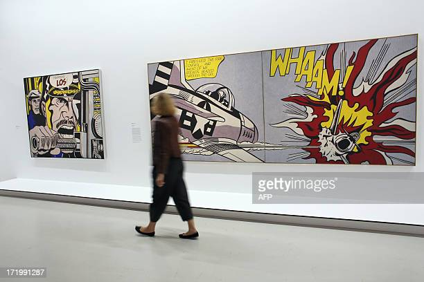 A visitor passes by the artworks 'TorpedoLos' and 'Whaam' by late US artist Roy Lichtenstein on June 30 2013 at the Centre Georges Pompidou...