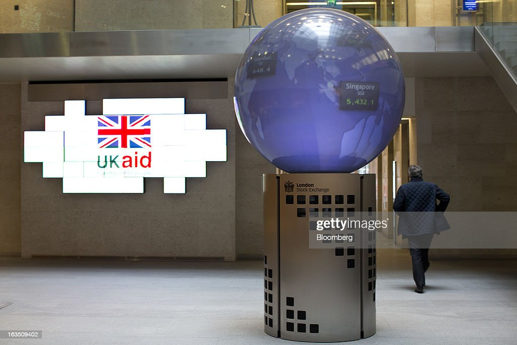 A visitor passes digital screens displaying a 'UK Aid' sign in the foyer of the London Stock Exchange Group Plc's (LSE) headquarters in London, U.K., on Monday, March 11, 2013. European stocks fell from a 4 1/2-year high as Fitch Ratings downgraded Italy and China's retail sales and industrial output missed forecasts. Photographer: Jason Alden/Bloomberg via Getty Images