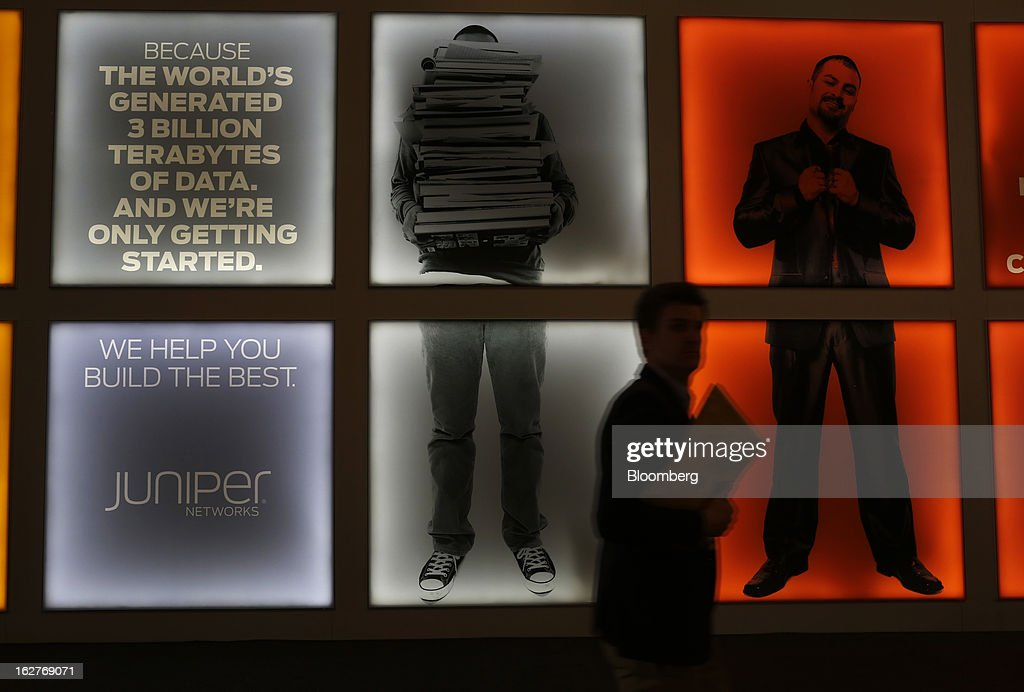A visitor passes illuminated advertisements outside the Juniper Networks Inc. pavilion at the Mobile World Congress in Barcelona, Spain, on Tuesday, Feb. 26, 2013. The Mobile World Congress, where 1,500 exhibitors converge to discuss the future of wireless communication, is a global showcase for the mobile technology industry and runs from Feb. 25 through Feb. 28. Photographer: Simon Dawson/Bloomberg via Getty Images