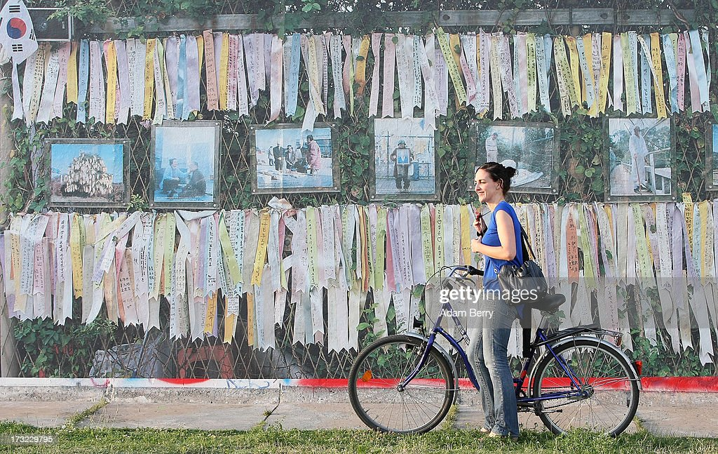 A visitor passes in front of a photo of the Freedom Bridge at the North and South Korean border as it hangs as part of the 'Wall on Wall' exhibition at the East Side Gallery section of the former Berlin Wall on July 10, 2013 in Berlin, Germany. A series of photos shot since 2006 by photographer Kai Wiedenhoefer hanging on the Western, river Spree side of the Wall features large pictures of separation barriers in Baghdad, Korea, Cyprus, Mexico, Morocco, Israel, Belfast, and in the former East Germany itself. The opposite side of the stretch of the original Wall is known as East Side Gallery, a memorial to peace and freedom covered in murals questioning the legacy of the original Wall, and the subject of several demonstrations earlier in March this year when sections of it were threatened with removal to make way for a construction site for luxury apartment buildings, discussion of which is still ongoing with a decision expected to be reached in early August.