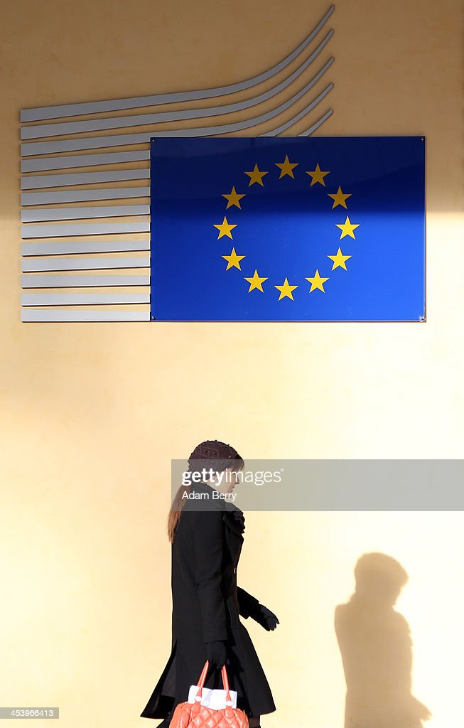A visitor passes the Berlaymont building of the European Commission (EC) on December 6, 2013 in Brussels, Belgium. The European Commission is responsible for the implementation and maintenance of the execution of the European Union's policies.