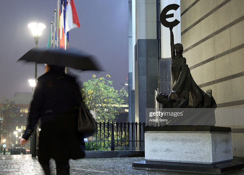 A visitor passes the 'Europe' sculpture by Belgian artist May Claerhout, depicting a woman holding up the symbol of the Euro, in the rain outside the European Parliament building on December 4, 2013 in Brussels, Belgium. The legislative body also has representation in Strasbourg and Brussels.