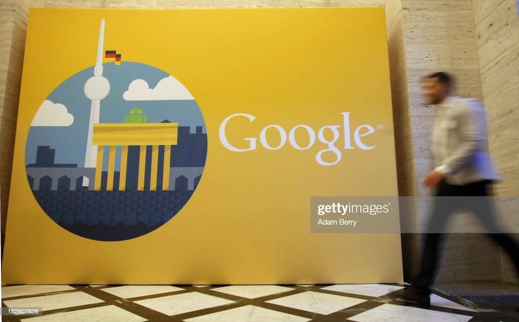 A visitor passes the Google logo next to an image of local monuments of the Brandenburg Gate and the Fernsehturm (TV tower) on September 26, 2012 in Berlin, Germany. Although the American company holds 95% of the German search engine market share and already has offices in Hamburg and Munich, its new offices on the prestigious Unter den Linden avenue are its first in the German capital. The Internet giant has been met with opposition in the country recently by the former president's wife, who has sued it based on search results for her name that she considers derogative. The European Commission has planned new data privacy regulations in a country where many residents opted in to have their homes pixeled out when the company introduced its Street View technology.