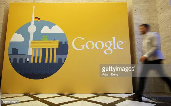 A visitor passes the Google logo next to an image of local monuments of the Brandenburg Gate and the Fernsehturm on September 26 2012 in Berlin...