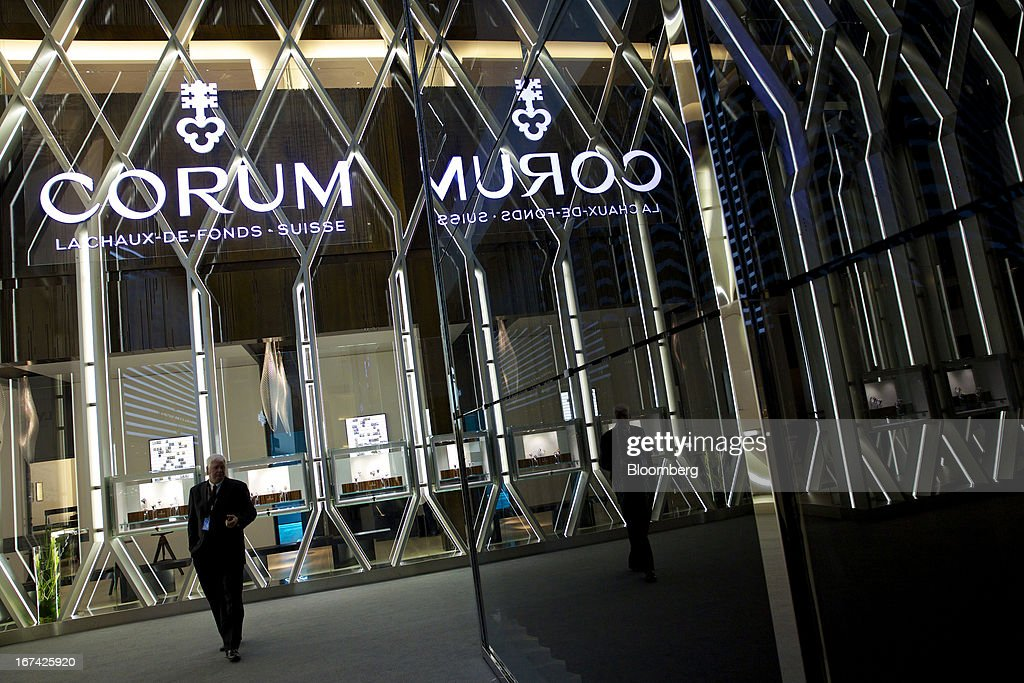 A visitor passes the Montres Corum booth at the Baselworld watch fair in Basel, Switzerland, on Thursday, April 25, 2013. The annual fair attracts 2,000 companies from the watch, jewelry and gem industries to show their new wares to more than 100,000 visitors. Photographer: Gianluca Colla/Bloomberg via Getty Images