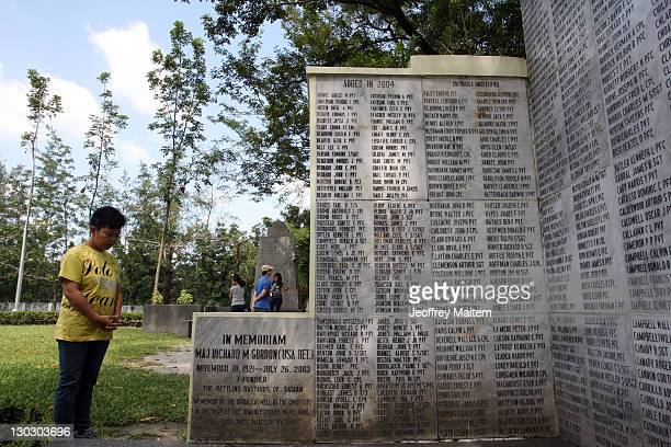 A visitor pays respects at a memorial inscribed with names of Filipino and US soldiers who died as prisoners of war from the Bataan Death March...