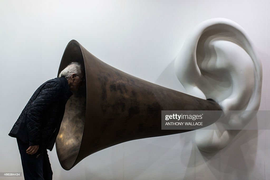 A visitor peers into US artist John Baldessari's 'Beethoven's Trumpet (With Ear) Opus # 133' at the Art Basel fair in Hong Kong on March 15, 2015. Hong Kong's biggest art fair, Art Basel, opened its doors with thousands of visitors expected for a city-wide canvas of creativity and commerce.