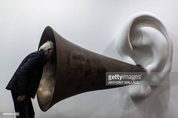 A visitor peers into US artist John Baldessari's 'Beethoven's Trumpet Opus' at the Art Basel fair in Hong Kong on March 15 2015 Hong Kong's biggest...