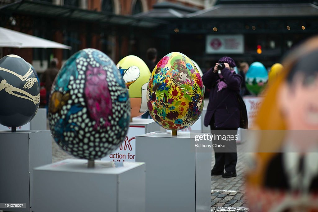 A visitor photographs a giant fibreglass easter egg entitled 'Many Of The Valleys Had Been' by John Biddle (foreground) which is on display in Covent Garden before the Big Egg Hunt on March 22, 2013 in London, England. Each egg is two and a half feet tall and designed by a leading artist.