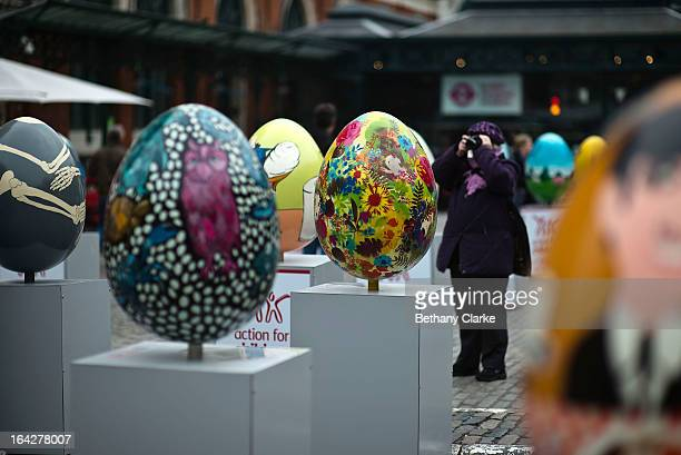 A visitor photographs a giant fibreglass easter egg entitled 'Many Of The Valleys Had Been' by John Biddle which is on display in Covent Garden...