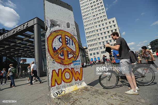 A visitor photographs a surviving portion of the former Berlin Wall at Potsdamer Platz on August 6 2014 in Berlin Germany Germany will commemorate...
