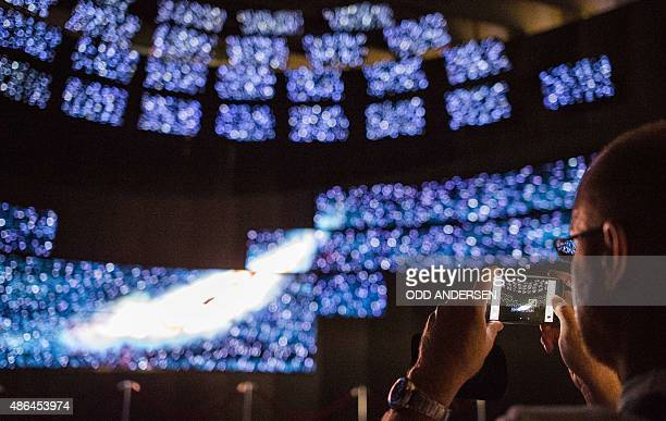 A visitor photographs a video wall at the South Korean electronics and home appliances manufacturer LG's booth on the opening day of the 55th IFA...