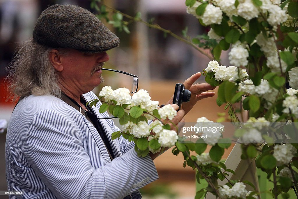 A visitor photographs flowers on a stand at the Chelsea Flower Show on May 20, 2013 in London, England. The Chelsea Flower Show run by the RHS, (Royal Horticultural Society) celebrates its 100th birthday this year.