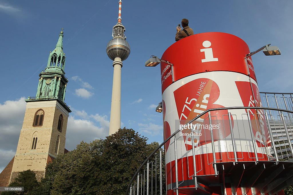 A visitor photographs the 18th-century St. Marienkirche church (its foundations date back to the 13th century) and the 20th-century broadcast tower at Alexanderplatz from an information tower to mark the 775th anniversary of the city on September 6, 2012 in Berlin, Germany. The city of Berlin is currently holding a series of exhibitions and events ahead of its 775th anniversary, which it will celebrate at the end of October. Berlin's sister settlement of Coelln is first referred to in a document from 1237, and by the beginning of the 14th century Coelln and Berlin, which stood on either side of the Spree River, joined together to become the region's most important trading center.