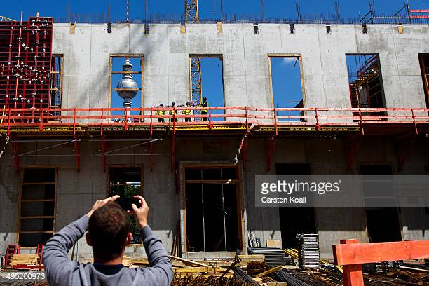 A visitor photographs the construction work of the Berlin City Palace in the city center which opened to visitors June 1 2014 in Berlin Germany The...