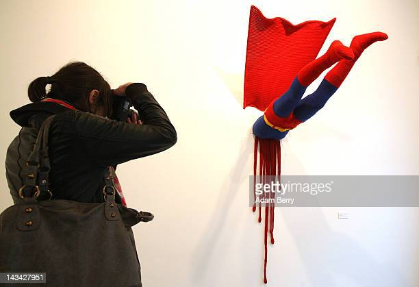 A visitor photographs the knitted sculpture 'Superman' by Patricia Waller featuring the comic book character meeting death by his own superhuman...